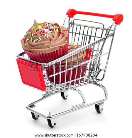 some cupcakes topped with a chocolate frosting in a shopping cart on a white background - stock photo