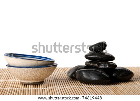 Some dark stones and two cups lie on mat