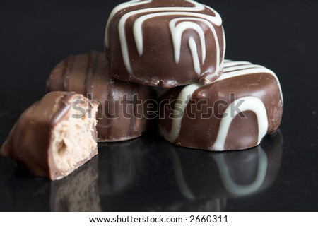 Some delicious chocolates lying together on a black background with reflection - stock photo