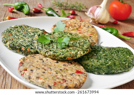 some different raw veggie burgers in a plate on a rustic wooden table - stock photo