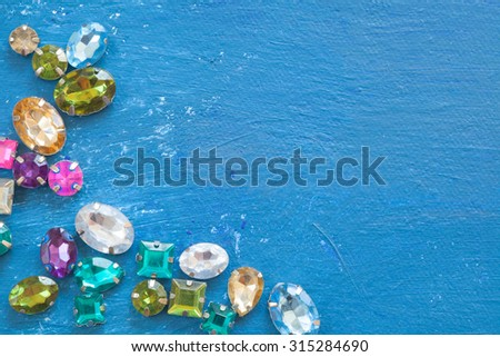 Some different toy gems jewels laying on a blue background - stock photo
