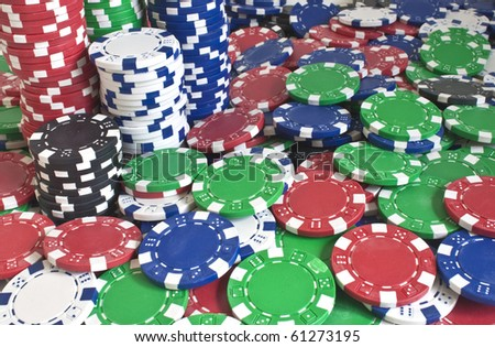 some different valued poker chips stacked and scattered