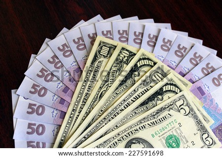 Some dollars and grivnas banknotes on dark background - stock photo