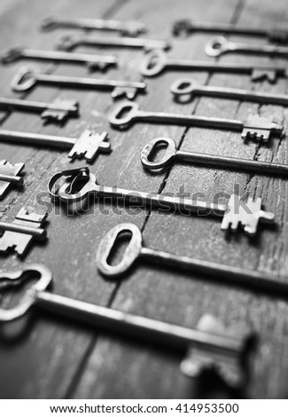 Some door keys aligned on old wooden surface, safety and security concept background - stock photo