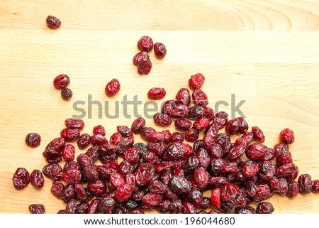 Some dried cranberries on a wooden background. - stock photo