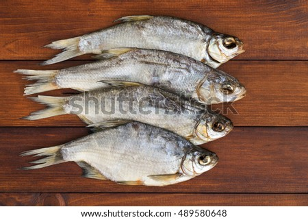 some dried fish on a light brown wooden background