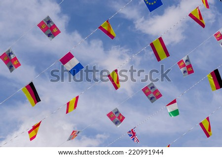 Some European flags over the sky in an spanish festive day. - stock photo