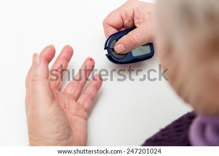 some female senior adult hands with glucometer  - stock photo
