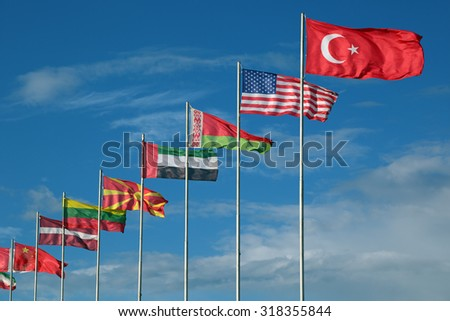 Some flags of the different countries on flagstaffs - stock photo