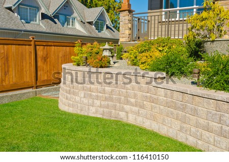 Some flowers and nicely trimmed bushes on the leveled front yard. Landscape design. - stock photo