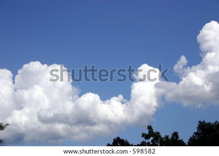 Some fluffy white clouds making a great formation in this deep blue sky - stock photo