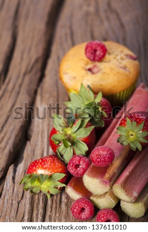 Some fresh and delicious fruits ingredients for muffins on a old wooden board - stock photo