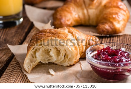 Some fresh baked Croissants on vintage wooden background - stock photo