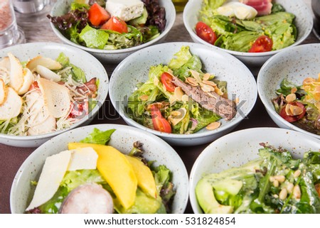 some fresh salad with many ingredients, mixed in grey dish