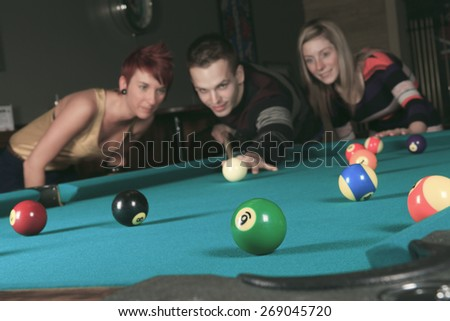 some friends play snooker in a bar.