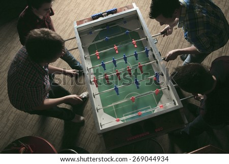 Some friends play soccer table in a bar. - stock photo