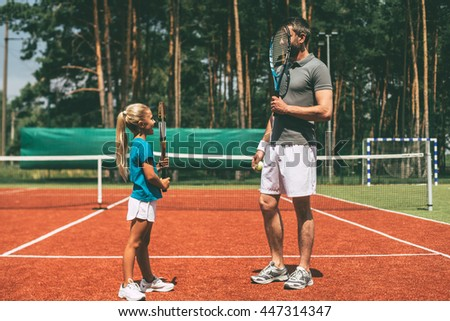 Some fun before the game. Full length of little blond hair girl and her father wearing sports clothing and carrying tennis rackets in front of their faces while standing on tennis court together