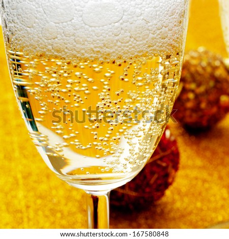 some glasses with champagne and some christmas balls in the background - stock photo
