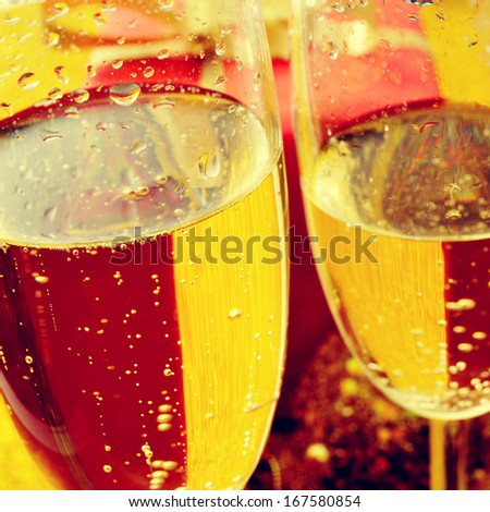 some glasses with champagne and some gifts and christmas balls in the background - stock photo