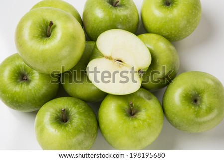 Some green apples on a white background seen from above.