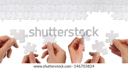 some hands hold a part of a puzzles to solve it