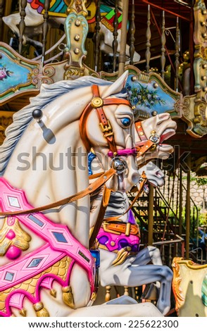 Some horses in a carousel. Funny attraction for childs - stock photo