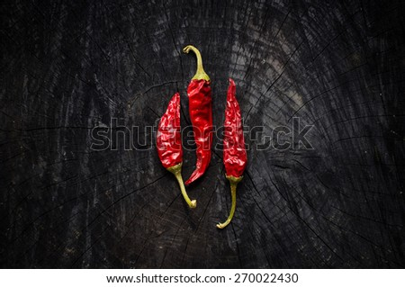 Some hot red peppers lie on a dark board - stock photo