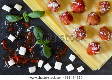 Some ingredients used to prepare lasagna following an old neapolitan recipe: raw lasagna sheets, small meatballs in tomato sauce,small mozzarella cheese pieces, basil and grated parmesan cheese. - stock photo
