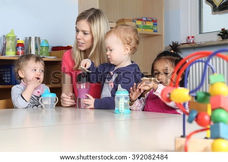 Some Kindergarten or nursery kids on a table drinking and playing  - stock photo
