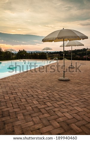 some luxurious parasols on the poolside at dusk - stock photo