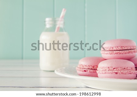 Some macarons on a plate and a school milk bottle with a straw on a white wooden table with a robin egg blue background. Vintage look. - stock photo