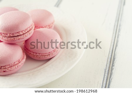 Some macarons on a plate over a white wooden table. Vintage style. - stock photo