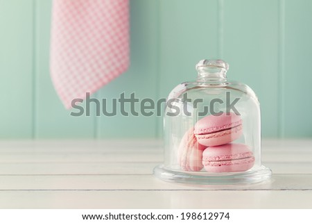 Some macaroons in a glass bell jar on a white wooden table with a robin egg blue background and a pink checkered napkin. Vintage Style. - stock photo