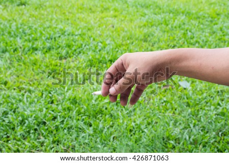 Some man holding a cigarette and a smoke and blur green grass background