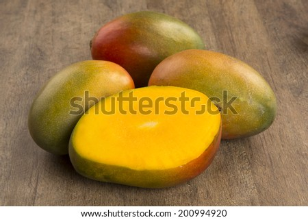 Some mangoes over a wooden surface