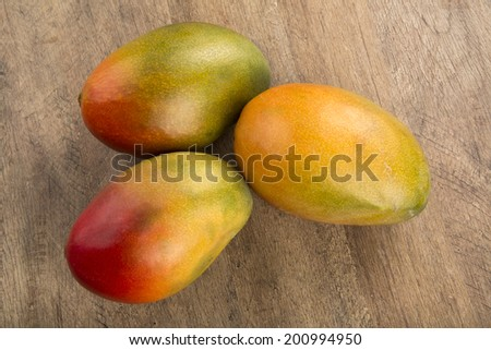 Some mangoes over a wooden surface seem from above - stock photo