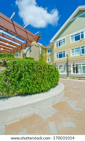 Some nicely trimmed bushes on the leveled and stoned bed on the paved plaza, court. Landscape urban design. Vertical. - stock photo