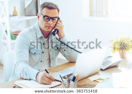 Some notes for the day. Handsome mature man talking on phone and making some notes while sitting at his working place - stock photo