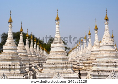 Some of the 729 stupas at Kuthodaw Pagoda, known as the world's largest book, in Mandalay, Myanmar. Each stupa houses a marble slab inscribed with a page of the Tipitaka book of Theravada Buddhism. - stock photo