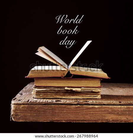 some old books on a rustic wooden table and the text world book day written in white on a black background - stock photo