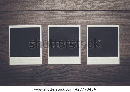 some old photos on brown wooden table background - stock photo