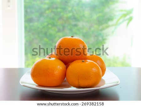 Some oranges are on dish which put on wooden table and in front of blurry background - stock photo