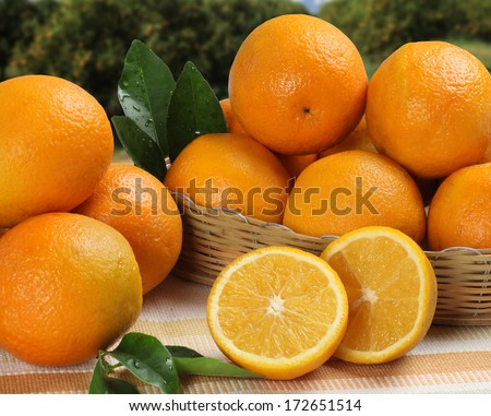 Some oranges in a basket over a wooden surface on a orange field as background - stock photo