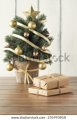 Some paper parcels wrapped tied with tags. Christmas gift boxes wrapped with paper kraft and tied with red & white baker's twine on a wooden table. Vintage Style. - stock photo