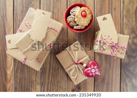 Some paper parcels wrapped tied with tags. Some cookies, a red heart and some christmas gift boxes wrapped with paper kraft and tied with red & white baker's twine on a wooden table. Vintage Style. - stock photo