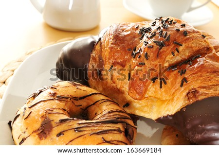 some pastries on a plate and a cup of coffee and a milk pot on a table - stock photo