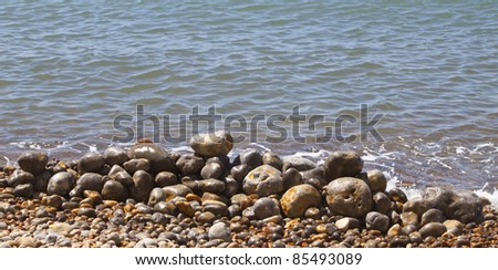 some pebbles stacked up on a pebbly beach close to the waters edge - stock photo