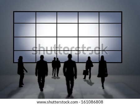 Some people (silhouettes) looking to a very big tv panel - stock photo