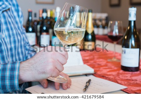 Some person's hand holding a glass of white wine for tasting.