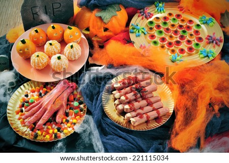 some plates with Halloween food, such as candies, scary fingers or mandarines as pumpkins, with different scary ornaments as spiders, cobwebs or a tombstone - stock photo